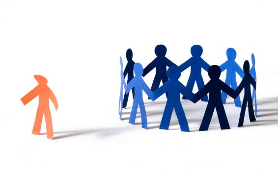 Orange paper person with dejected stance off to the side of a circle of blue paper people