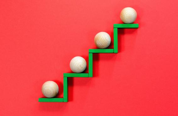 Four wooden balls on a green stair-step pattern of wooden planks against a red background