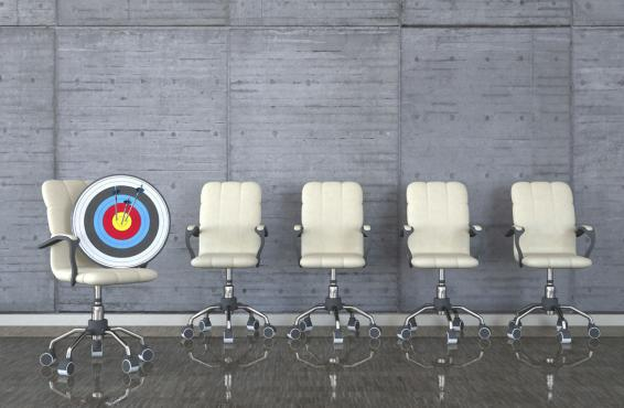 A line of five white office chairs against a grey wall, with the first the first chair holding an archery target pierced by three arrows.