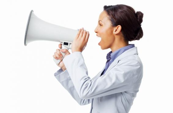 A doctor in profile speaking through a white megaphone against a white background.
