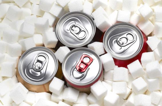 The tops of four aluminum pop-top cans, surrounded by sugar cubes.
