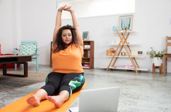 Woman in workout clothes, sitting in her living room, stretching her arms above her head as she sits on a yoga mat.