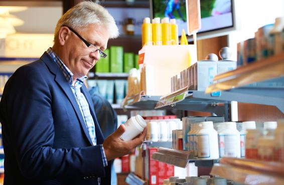 Man in pharmacy looking at medicine bottle.