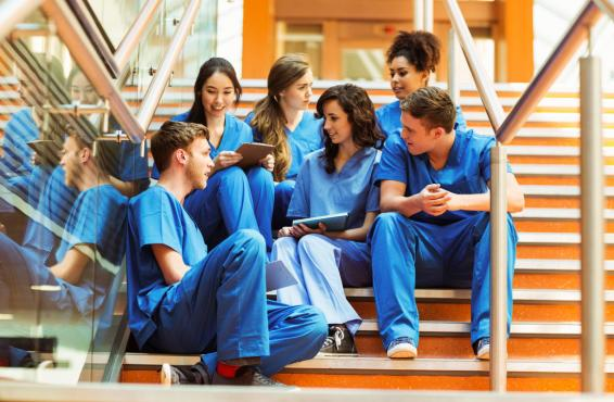 Group of medical school students in blue scrubs, sitting on the stairs