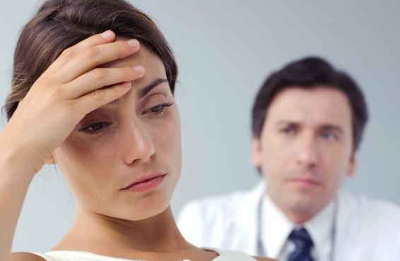 Patient in discomfort with physician looking on.