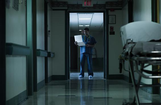 Physician standing in the doorway of a hospital hallway.