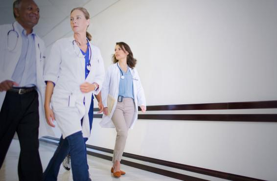 Four physicians walking down a hallway.