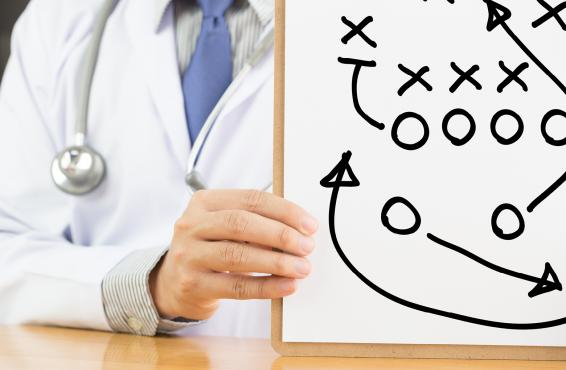 Physician holding up a football play chart.