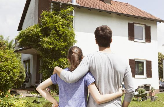 Couple arm in arm looking at a house.