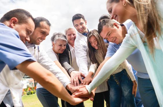 Medical professionals putting their hands together in the middle of a group circle