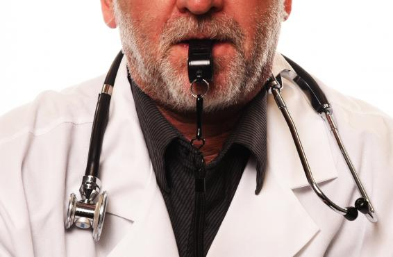 A doctor with a stethoscope around his neck and a whistle in his mouth