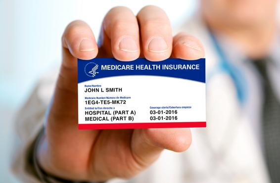 A man holding an example of a Medicare card.
