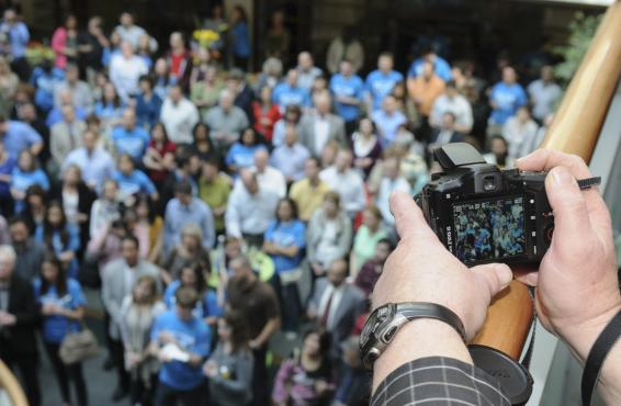 A man takes a picture of a crowd from a balcony.