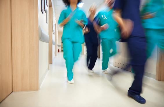 An action shot of a diverse group of doctors running through a hallway.