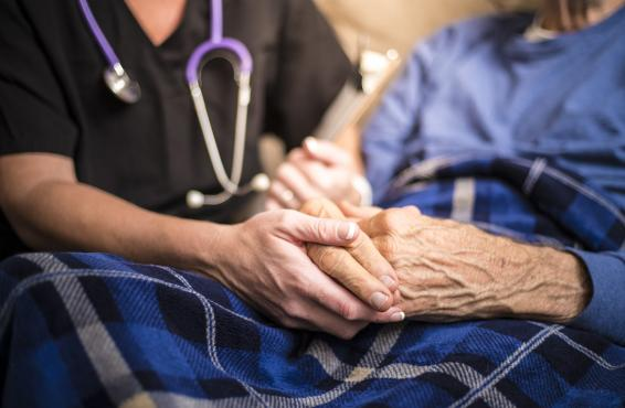 A doctor holding an old person's hands while giving care.