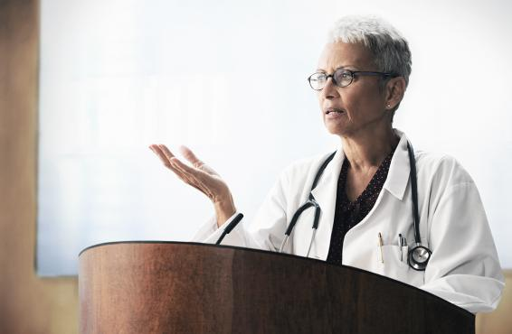 Female physician at podium.